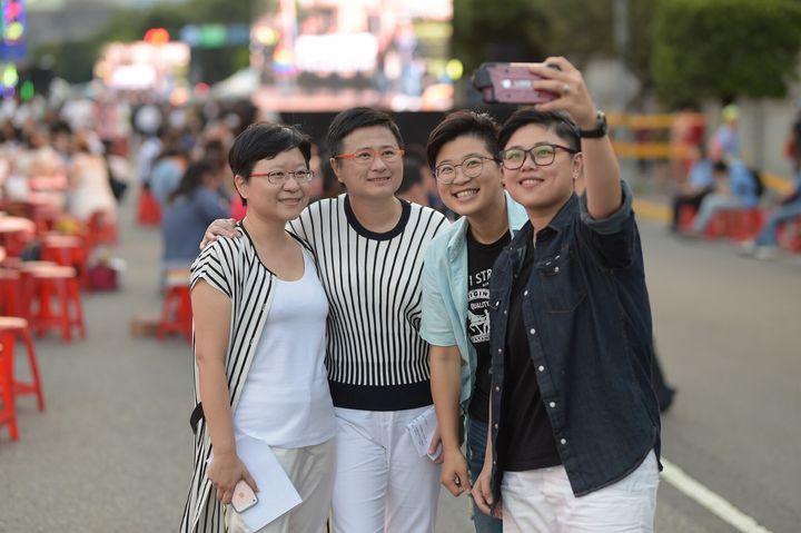 来場者と写真を撮影する許秀雯さん(左から二番目)。左はパートナーの簡至潔さん