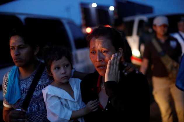 A woman, part of a convoy of Central American migrants, is escorted into a van by National Institute...