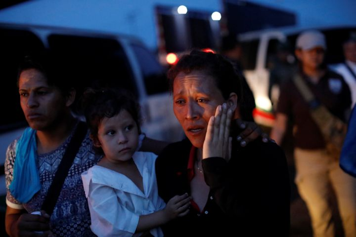 A woman, part of a convoy of Central American migrants, is escorted into a van by National Institute of Migration (INM) officers, after being detained at a checkpoint on the outskirts of Tapachula, Mexico on May 19, 2019.