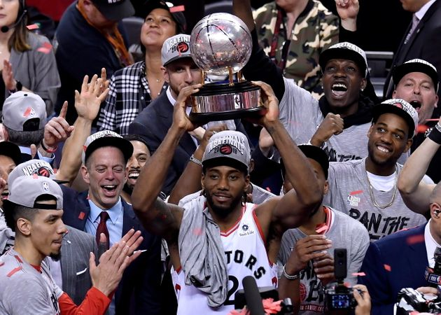Toronto Raptors forward Kawhi Leonard holds up the trophy after the team's 100-94 win over the Milwaukee...