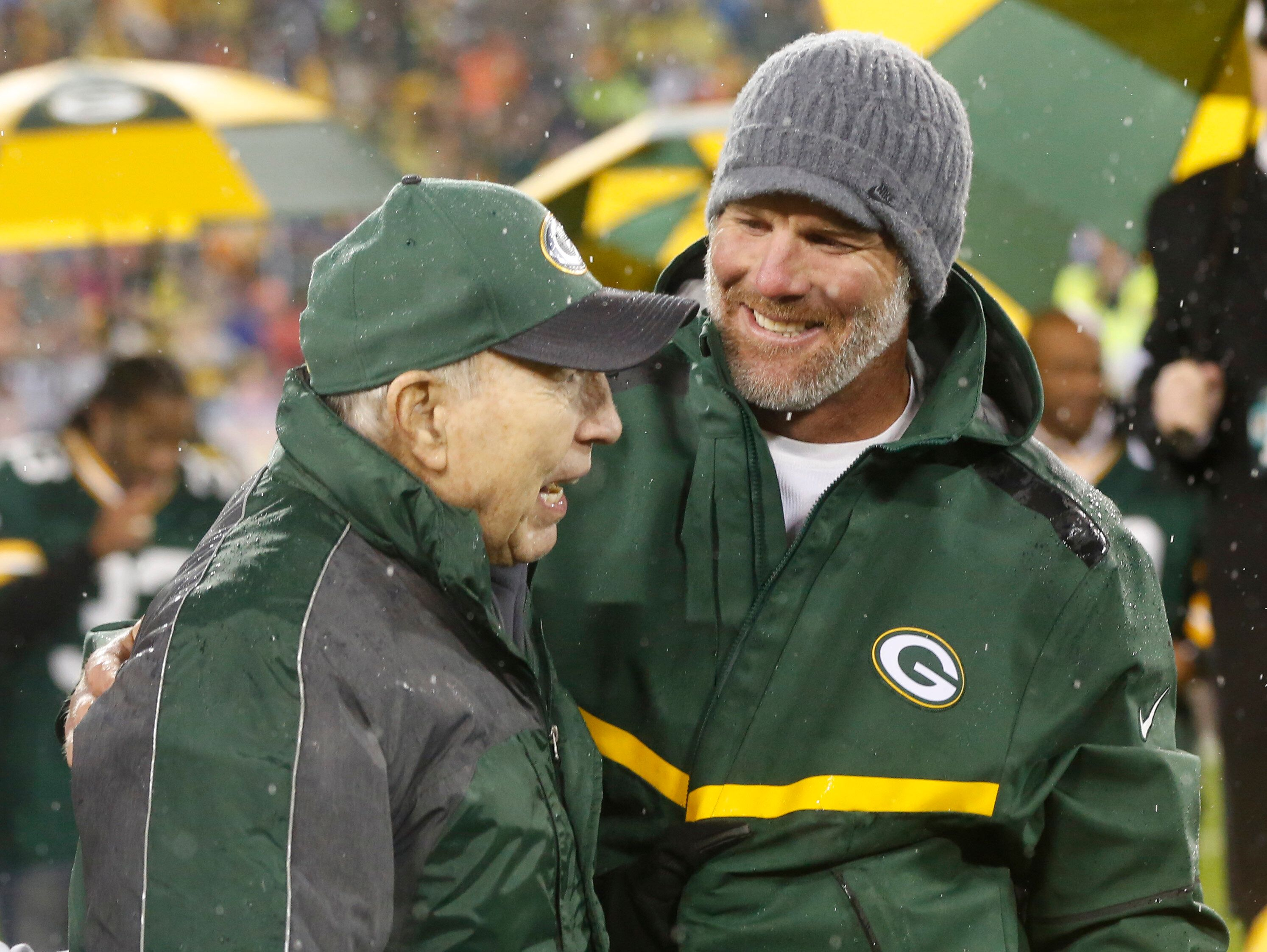 Brett Favre smiles with Bart Starr during a ceremony at halftime of an NFL football game between the Green Bay Packers and Chicago Bears Thursday, Nov. 26, 2015, in Green Bay, Wis. Favre's retired No. 4 and name were unveiled inside Lambeau Field during the ceremony. (AP Photo/Mike Roemer)