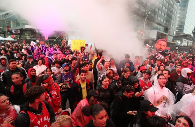 Fans line up in the rain for Jurassic Park as the Toronto Raptors play the Milwaukee Bucks in Toronto...