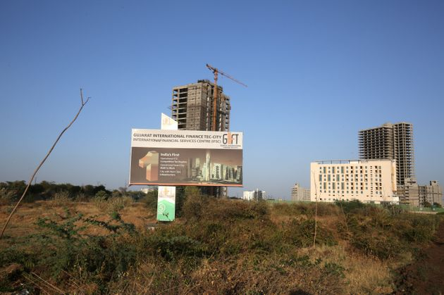A billboard stands in front of buildings under construction at the Gujarat International Finance Tec-City...