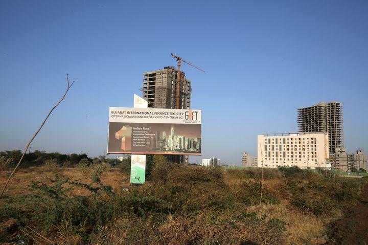 A billboard stands in front of buildings under construction at the Gujarat International Finance Tec-City (GIFT) at Gandhinagar, Gujarat, March 20, 2019.