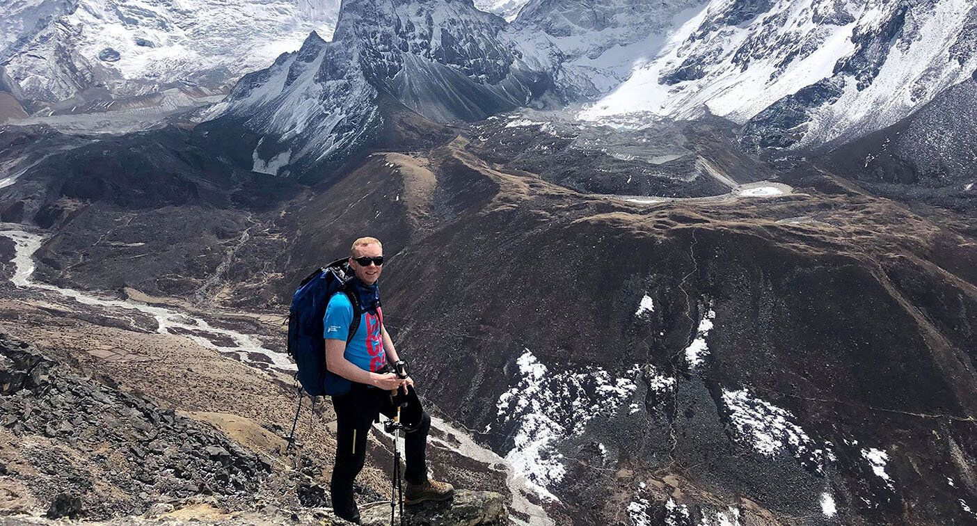 Robbie Fisher stands in front of a ravine and snowy mountain peaks.