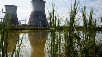 FILE - In this Wednesday, Sept. 7, 2016 file photo, two cooling towers can be seen in the reflection of a pond outside of the Bellefonte Nuclear Plant, in Hollywood, Ala. The Tennessee Valley Authority has sold the unfinished nuclear power plant for $111 million. Nuclear Holdings LLC purchased the Bellefonte Nuclear Plant at an auction Monday, Nov. 14, 2016. The sale price was more than three times the minimum bid of $36.4 million. (AP Photo/Brynn Anderson, File)