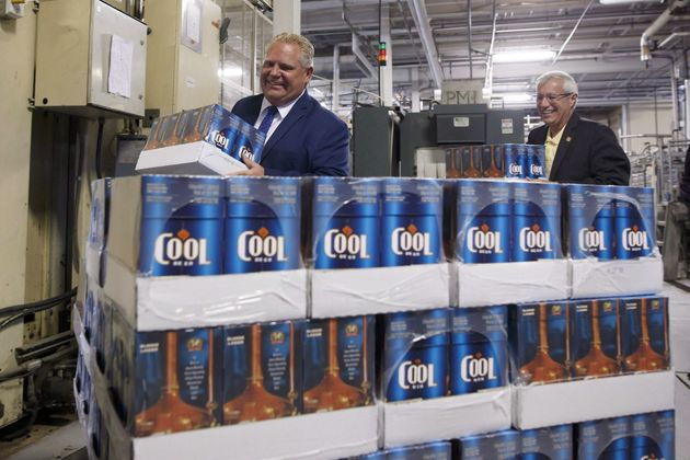 Ontario Premier Doug Ford and Finance Minister Vic Fedeli stack cases of beer during a photo opportunity...