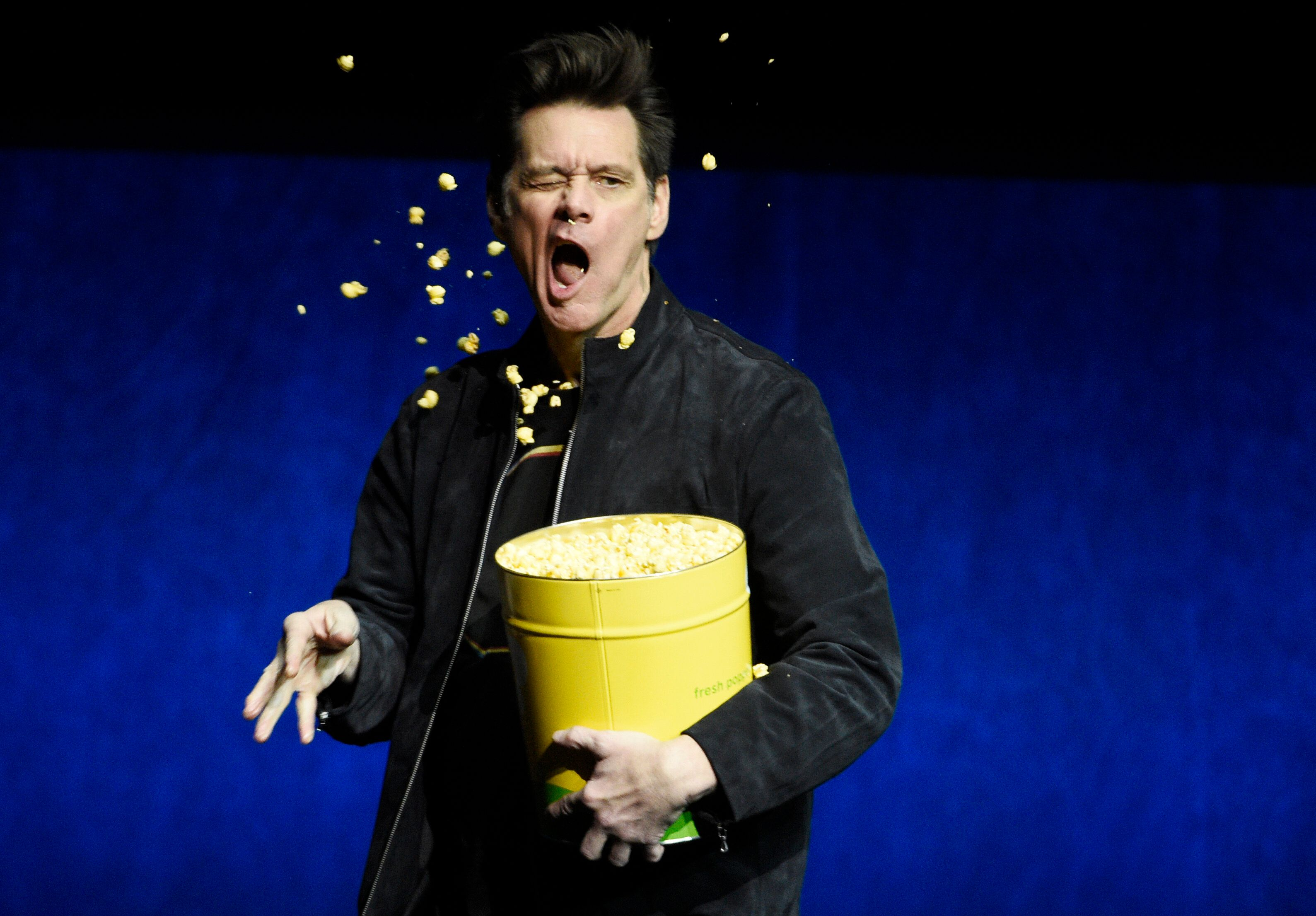 """Jim Carrey, a cast member in the upcoming film """"Sonic the Hedgehog,"""" throws popcorn into his face during the Paramount Pictures presentation at CinemaCon 2019, the official convention of the National Association of Theatre Owners (NATO) at Caesars Palace, Thursday, April 4, 2019, in Las Vegas. (Photo by Chris Pizzello/Invision/AP)"""
