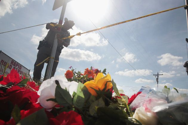 A police officer ties off crime scene tape near a small memorial close to the First Baptist Church of Sutherland Springs on Nov. 7, 2017 in Sutherland Springs, Texas.