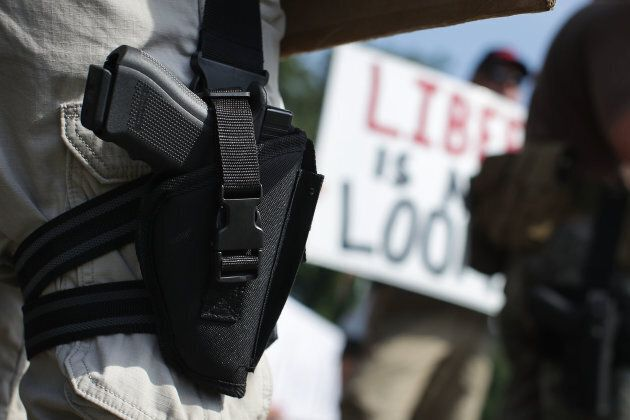 An armed gun rights activist counter-protests during a gun control rally outside the headquarters of...