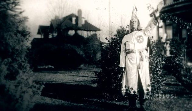 A Klu Klux Klan member posing in a still from the Telus documentary,
