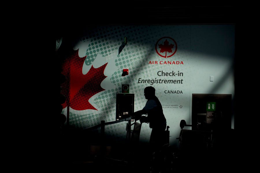 The silhouette of an Air Canada employee is seen near a check-in counter at Toronto Pearson International...