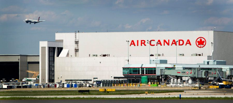 A plane passes over an Air Canada hangar at Toronto Pearson International Airport on Aug. 30,