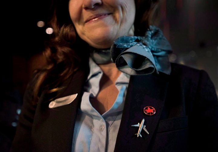 A flight attendant smiles while posing at Air Canada's annual general meeting in Toronto on May 12, 2015.
