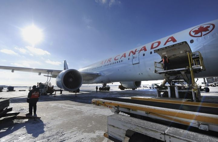 Ground crew workers load baggage into an Air Canada flight on Jan. 8, 2014 in Toronto.