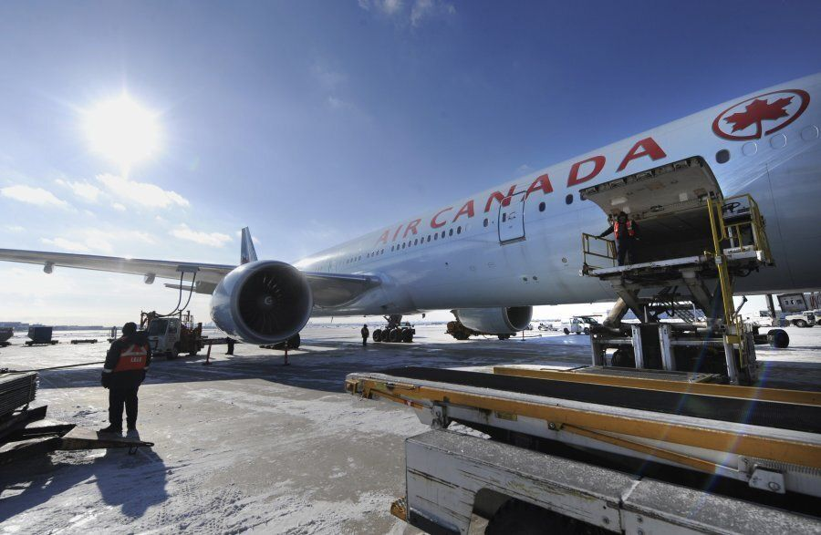 Ground crew workers load baggage into an Air Canada flight on Jan. 8, 2014 in