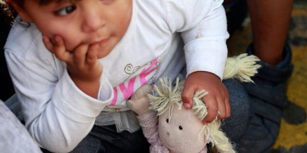 A member of a migrant family from Mexico, fleeing from violence, holds her doll while waiting to enter...