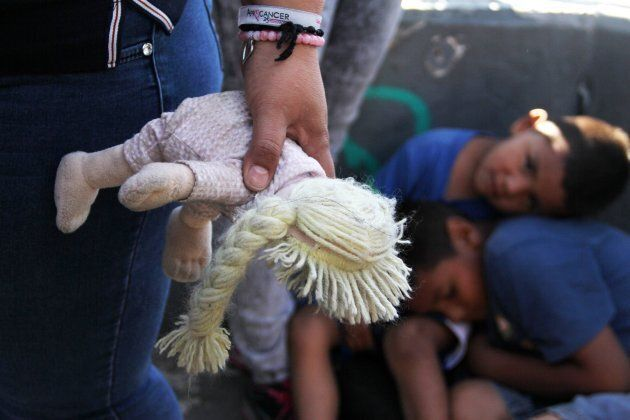 A Mexican woman holds a doll next to children at the Paso Del Norte Port of Entry, in the U.S.-Mexico...