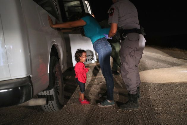 A two-year-old Honduran asylum seeker cries as her mother is searched and detained near the U.S.-Mexico...