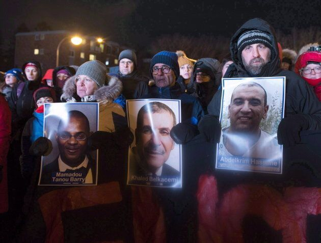 People hold pictures of the victims at a vigil to commemorate the one-year anniversary of the Quebec...