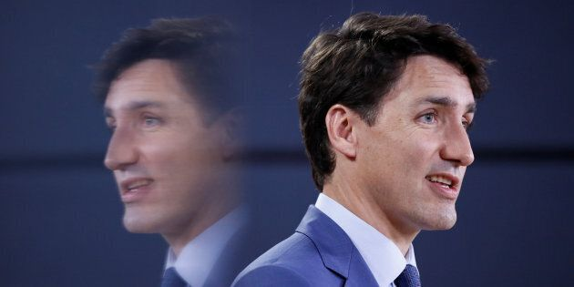 Prime Minister Justin Trudeau is reflected in a monitor while speaking during a news conference in Ottawa...