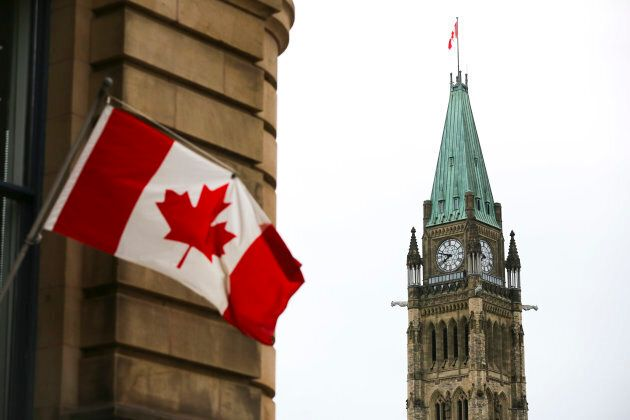 The Canadian Flag flies on a building in Ottawa across from the Peace Tower on Centre Block of Parliament Hill.