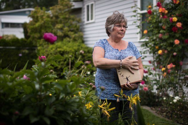 Wendy Gould holds the cremated remains of her late husband George Gould at her home, in Aldergrove, B.C. on May 25, 2018.