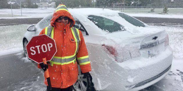 A crossing guard stands near Gander Elementary school on June 26,