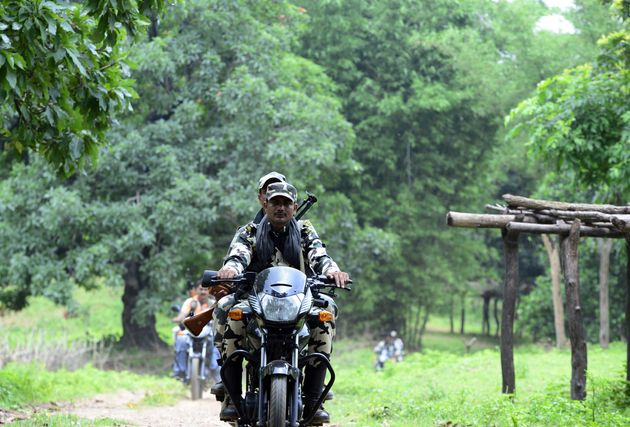 CRPF personnel drive by motorbike to conduct patrols through a village in Giridih district of