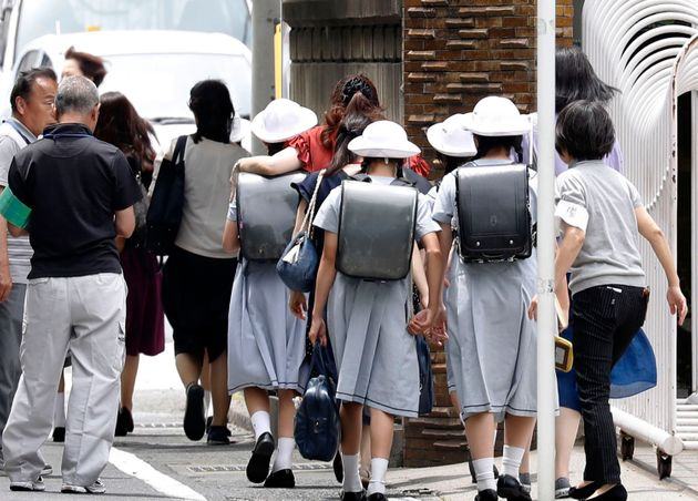 Elementary School students leave their school with parents following an attack in Kawasaki, near