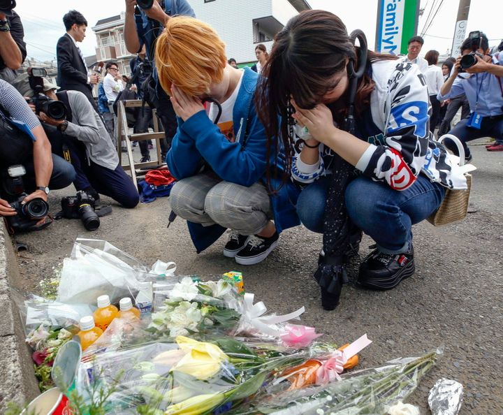 Women pray after offering flowers near the scene of a deadly knife attack in Kawasaka, Japan, which is just outside of Tokyo, on May 28, 2019.