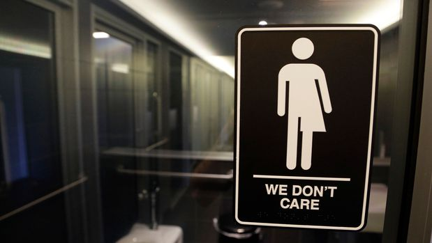 """FILE - In this May 12, 2016, file photo, signage hangs outside a restroom at 21c Museum Hotel in Durham, N.C. Transgender plaintiffs who think the compromise that replaced North Carolina's """"bathroom bill"""" is still discriminatory are heading to court. A federal judge will hear arguments Monday, June 25, 2018, from lawyers representing Republican legislative leaders who say the case should be dismissed because the plaintiffs can't prove the new law is harming them. (AP Photo/Gerry Broome, File)"""