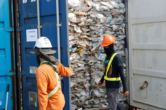 Workers open a container full of non-recyclable plastic detained by authorities at the west port in Klang,...
