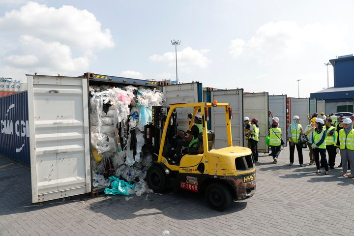 Officers from the Ministry of Environment examine a container full of non-recyclable plastic which was detained by authoritie