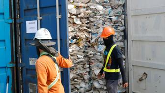 Workers open a container full of non-recyclable plastic detained by authorities at the west port in Klang, Malaysia, Tuesday, May 28, 2019. Malaysia environment minister Yeo Bee Yin says Malaysia has become a dumping ground for the world's plastic waste, and the country has begun sending non-recyclable plastic scrap to the developed countries of origin. (AP Photo/Vincent Thian)