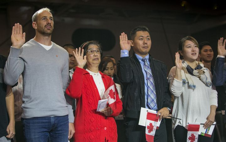 New citizens swear their allegiance to Canada during a citizenship ceremony in Vancouver on July 1, 2016. A new bill proposed by the Liberals aims to change the words of Canada's oath of citizenship.