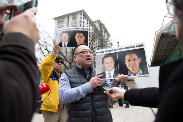 Louis Huang of Vancouver Freedom and Democracy for China holds photos of Canadians Michael Spavor and...