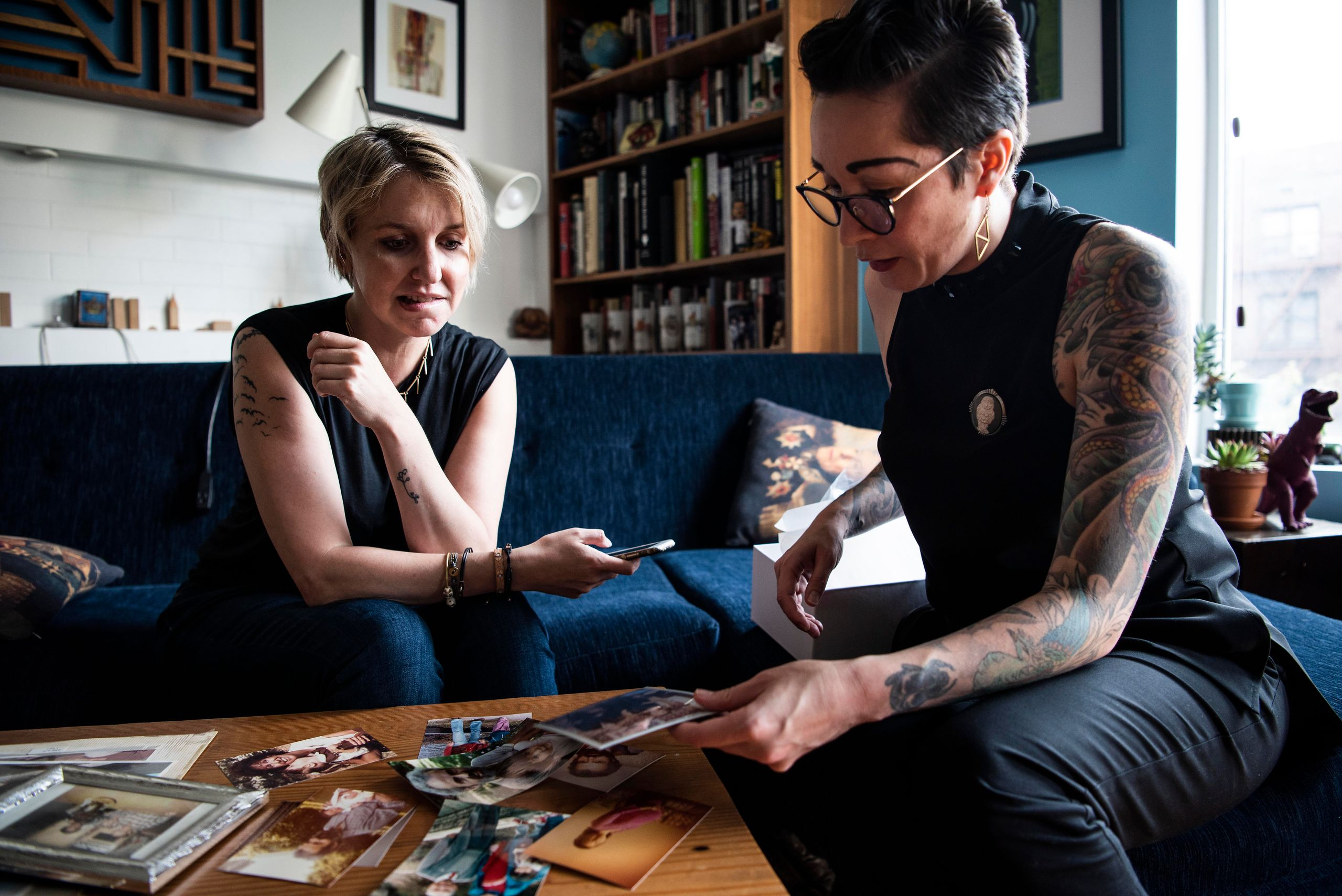 Jess McIntosh, left, and Ali Cole look over family pictures in Cole's Brooklyn, New York, home.