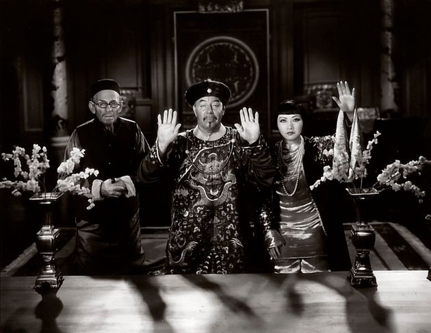 Actress Anna May Wong, at right, and actors E. Alyn Warren and Warner Oland -- two white men portraying...