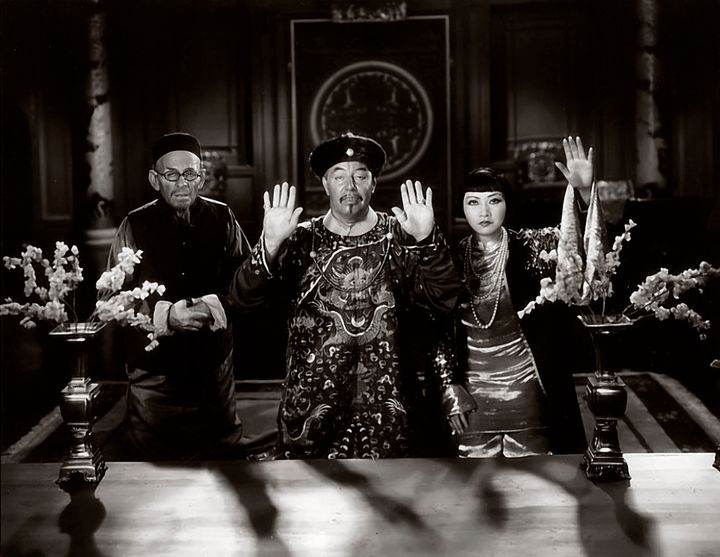 Actress Anna May Wong, at right, and actors E. Alyn Warren and Warner Oland -- two white men portraying Asians -- in a scene