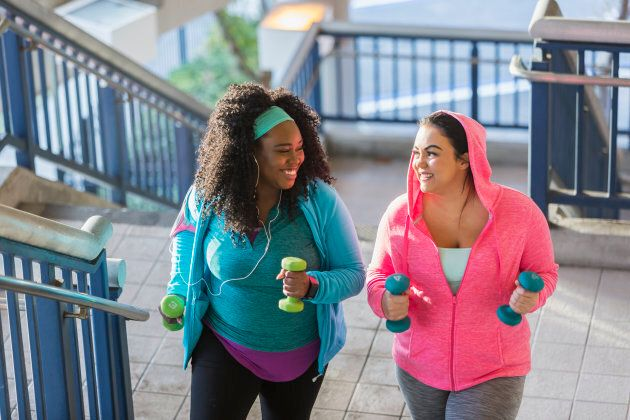 Two multi-ethnic young women exercising together. They are looking at each other, smiling, as they climb a staircase holding hand weights.