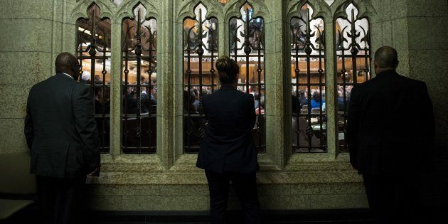 People listen from outside the chamber in the House of Commons on June 29, 2016 in