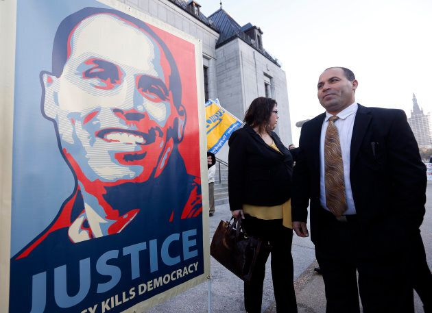 MMohamed Harkat looks at a sign held by supporters outside the Supreme Court of Canada in Ottawa on Oct. 10, 2013.