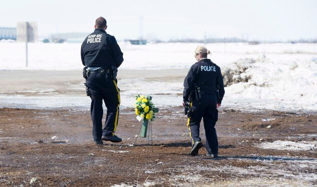 Members of the RCMP place flowers at the intersection of a crash site near Tisdale, Sask. on April, 8,