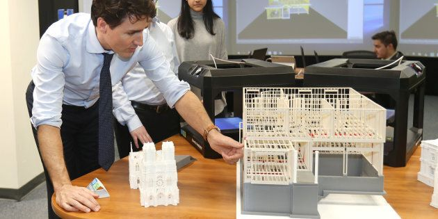 Prime Minister Justin Trudeau looks at construction models created by 3D printers at the George Brown...