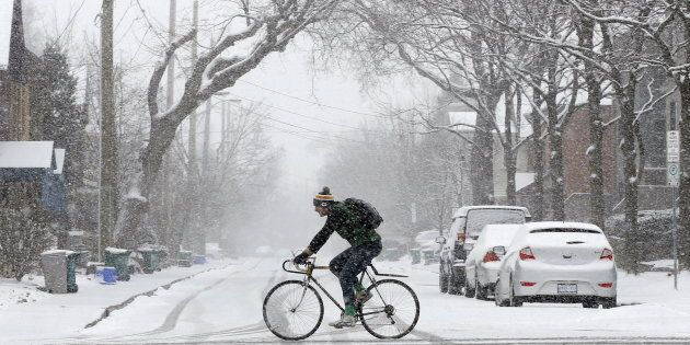 A man rides a bicycle during a spring snow storm in Ottawa, April 6,