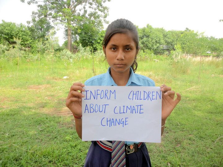 In Nepal, Sanchita, 12, holds a message reading 'Inform children about climate change.'