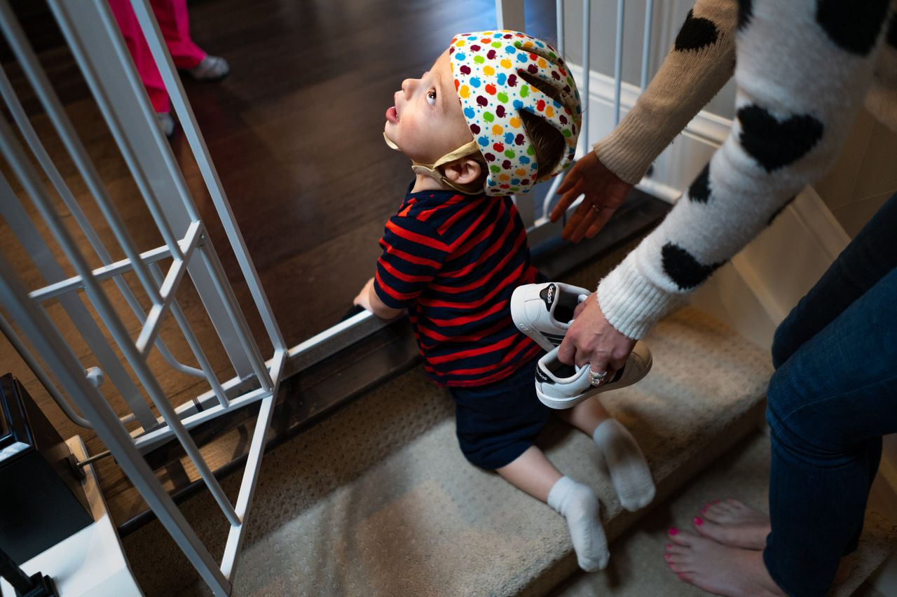 Maxwell Freed, who suffers from a rare genetic neurological disease, is helped to the top of a set of stairs at his home in Denver. Climbing the stairs is a new accomplishment for Maxwell, whose disease has delayed his physical and mental development.