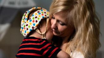 Amber Freed holds her son, Maxwell Freed, 2, during therapy session at their home Denver, Colo. on May 11, 2019. Maxwell suffers from a genetic disease affecting his neurological system, which if left untreated can lead to intellectual disabilities, debilitating seizures, behavioral problems and language impairments. Through 12 therapy sessions a week, Maxwell is working to overcome symptoms of his illness as he continues on a path toward meeting the standard milestones of physical and mental development. (Autumn Parry / For HuffPost)