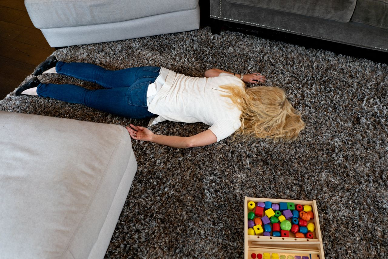 Amber lies on the floor of their family's home in a moment of exhaustion following her daily routine of caring for her twin children, one of whom suffers from a rare genetic disease.